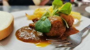 Mar y montaña de albóndigas en salsa de sepia y canónigos con patatas kennebec y escamas de sal negra (Restaurante Chasca).